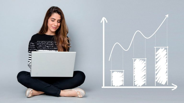 Mulher com um computador ao lado de metas