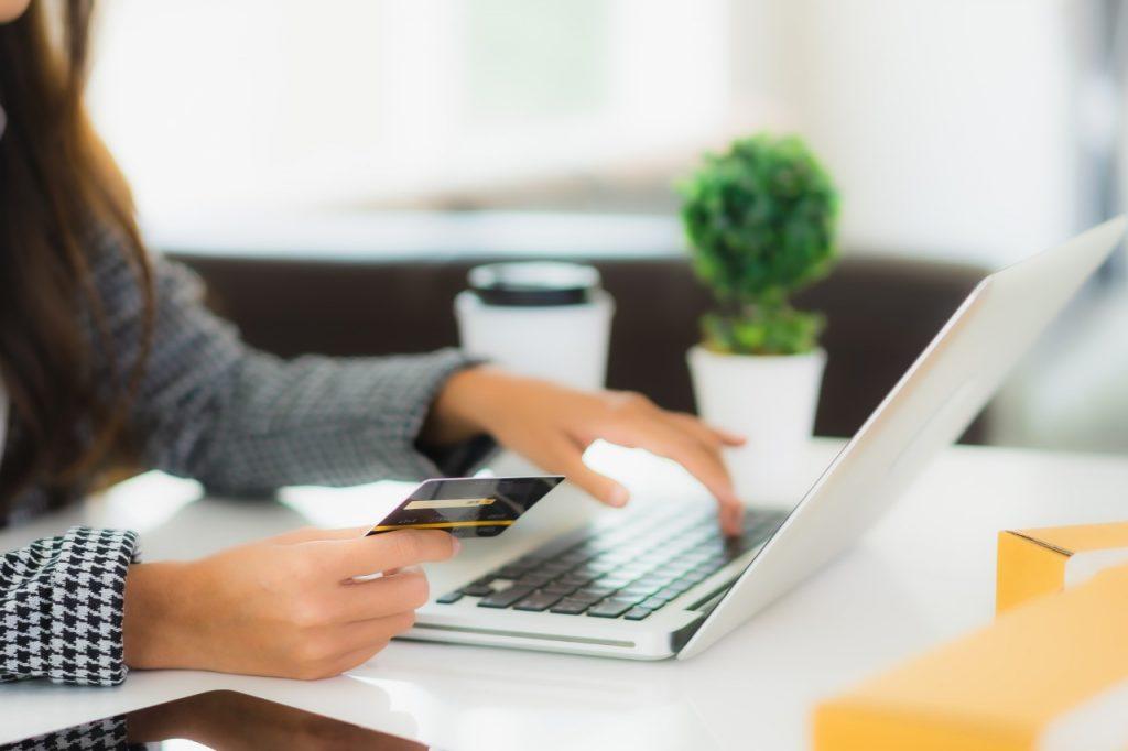 Mulher com cartão de crédito na frente do computador